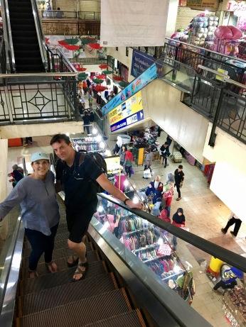 Going up an escalator in Pasar Baru